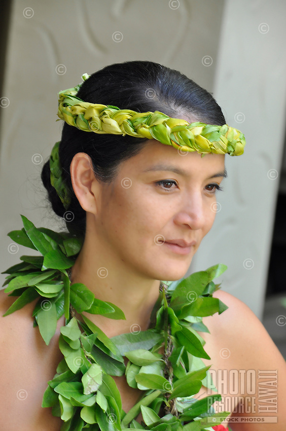 A hula dancer with an open-ended maile lei and a woven headband prepares before a performance at the Hilton Hawaiian Village resort in Waikiki, O'ahu.