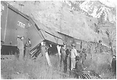 Refrigerator car #121 derailed and leaning.  It has been propped up while waiting for more assistance.  The crew and other personnel are just hanging around while help is on the way.<br /> RGS  Telluride Branch, CO  Taken by Virden, Walter - ca. 1913