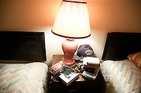 A nightstand in a small motel piled with fly fishing items during a fishing road trip to the Driftless Area of southwestern Wisconsin.
