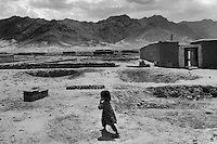 PARWAN DISTRICT, AFGHANISTAN - MAY 16. .A young girl walks past her home in Parwan Province. The East River Range, a place used as a firing range by the U.S. air force is seen in the distance. (Javier Manzano / For The Washington Post). ..
