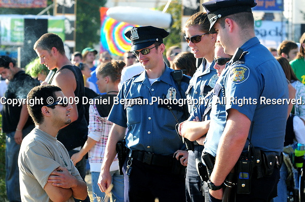 Seattle Police Department officers talk to a festivalgoer after instructing him to dump out a bong and it's contents into Elliott Bay, near the end of day 2 of Hempfest at Myrtle Edwards Park Sunday August 16, 2009. Photo by Daniel Berman/SeattlePI.com