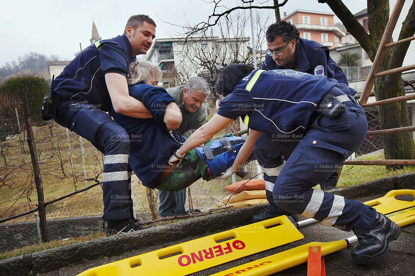 Switzerland. Canton Ticino. Comano. Paramedics team carry an injured man on an emergency medical stretcher. The man was cutting branches off a tree, fell on the ground and broke his right leg. He is brought to hospital for medical surgery and recovery. Three paramedics wear blue uniforms and work for the Croce Verde Lugano. Both men are professional certified nurses, the woman (R) is a volunteer specifically trained in emergency rescue. The Croce Verde Lugano is a private organization which ensure health safety by addressing different emergencies services and rescue services. Volunteering is generally considered an altruistic activity where an individual provides services for no financial or social gain to benefit another person, group or organization. Volunteering is also renowned for skill development and is often intended to promote goodness or to improve human quality of life. 27.01.2018 © 2018 Didier Ruef