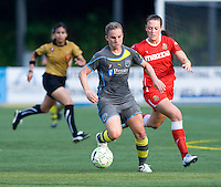 Amy Rodriguez (8) of the Philadelphia Independence carries the ball past Brittany Bock (21) of the Western New York Flash during the game at Quick Stadium in Chester, PA.  The Western New York Flash defeated the Philadelphia Independence, 2-1.