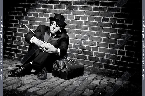 Charlie Chaplin mime Businessman in black suit down-and-out sitting on the street in a spot of light with his bag. Artistic humorous concept. Performing artist Peter Jarvis. Toronto Canada.