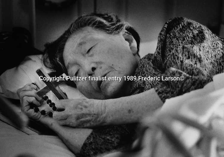 In the peaceful evening hours, a hibakusha at the Nagasaki-A-bomb nursing home turns to religion for strength as she grasps a crucifix to her heart.  Pulitzer finalist entry 1989 Frederic Larson©