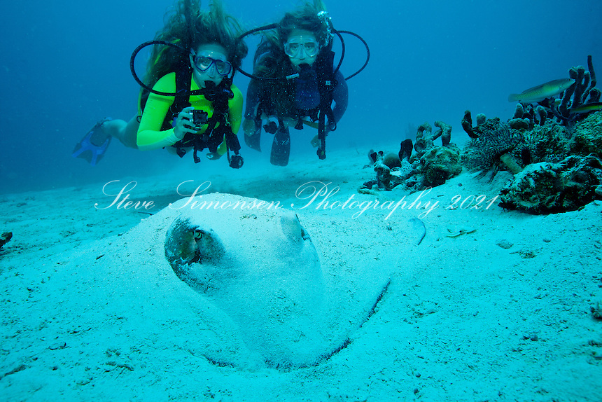Two teenage divers with a southern stingray<br /> Lind Point<br /> St. John, U.S. Virgin Islands