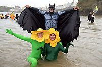 Pictured: People dresses as daffodils and in Batman fancy dress take to the water. Tuesday 26 December 2017<br /> Re: Hundreds took part in this year's Tenby Boxing Day Swim which sees people in fancy dress taking to the sea in Tenby, west Wales, UK.