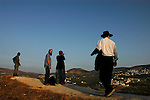 An Israeli soldier, a couple of settlers and an ultra-orthodox Jewish man, overview the landscape of a Palestinian village seen from the Israeli settlement of Sa-Nur, West Bank.<br /> Thousands of settlers gathered in Sa-Nur that day, to welcome and assist 13 settler families, which recently moved-in to the settlement, some 2 months before Sa-Nur is due to be evacuated as part of Israel's pullout from Gaza and the northern West Bank.