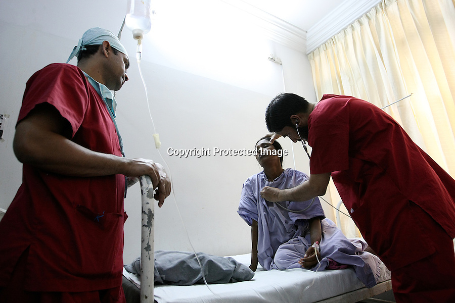 "In the pre-operation room of the Acid Survivors Foundation hospital, the anaesthesist is checking pulse of an acid victim who is about to have a surgery. Kakalie, a nurse working there explains : ""You have to understand that these people are living in countryside, in deserted places where they don't know what happens in hospitals or operation theatre. People we receive for the first time are usually very afraid. They didn't trust anaesthesia and they think they will wake up ""with everything open"", as they say. Others think they will not wake up."".Dhaka, Bangladesh - 2009"