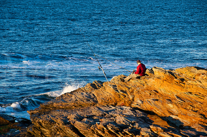 Man fishing from rocks.
