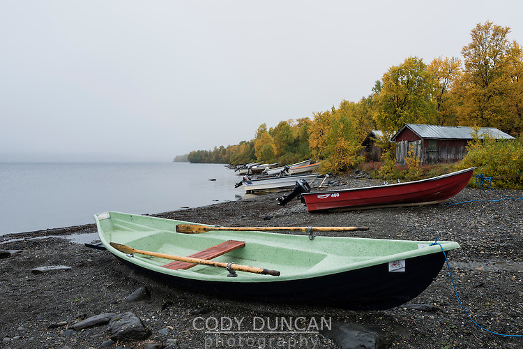 Boats on rocky shore of lake Stor-Tjulträsket, Ammarnäs, Lapland, Sweden