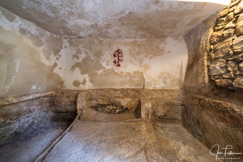 The interior of the Garden Tomb in Jerusalem, just north of the Damascus Gate and outside the walls of the ancient city.  The Garden Tomb is thought by many to be the burial place of Jesus Christ, rather than in the Church of the Holy Sepulchre.  Nearby is a hill thought by many to be Golgotha, the site of the crucifixion of Christ.  On the wall is a reproduction of the actual Byzantine cross discovered when the tomb was excated with alpha and omega symbols signifying Jesus Christ.
