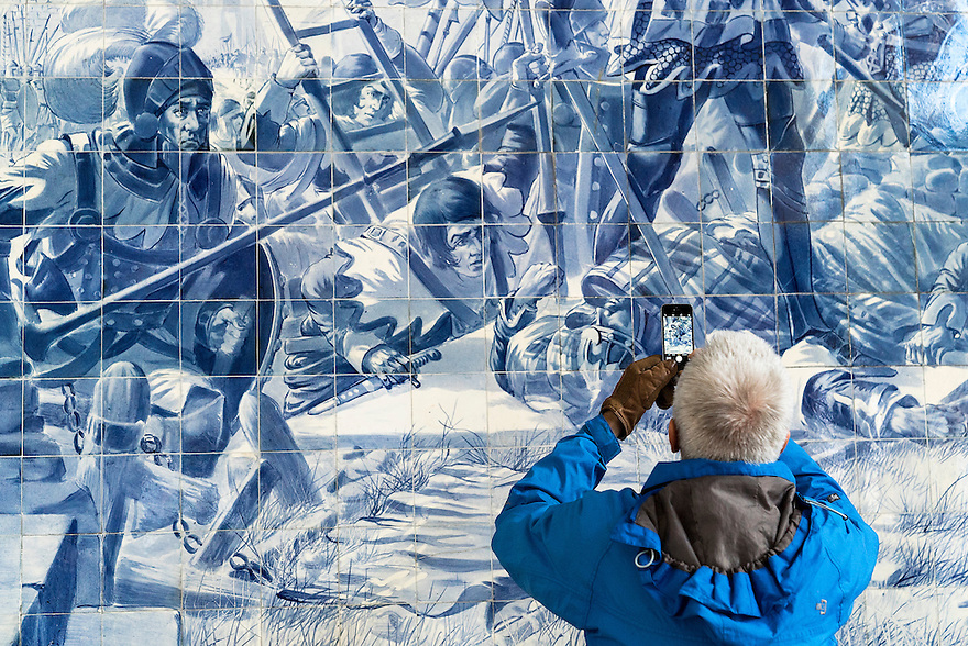 A tourist takes a photograph of the azules in São Bento Station in Oporto, Portugal