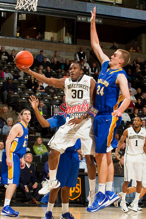 Travis McKie (30) of the Wake Forest Demon Deacons drives to the basket past Chris Uhle (24) of the Rollins Tars at the LJVM Coliseum on November 2, 2012 in Winston-Salem, North Carolina.  The Demon Deacons defeated the Tars 73-66.    (Brian Westerholt/Sports On Film)