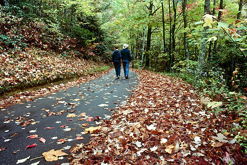 "Couple walks on community ""rails to trails"" walking trail in fall"