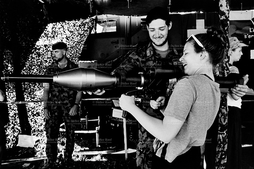 """Switzerland. Canton Fribourg. Estavayer. A young woman is testing a Panzerfaust weapon on a swiss army stall during the Federal Wrestling and Alpine Games Festival. The Panzerfaust 3 (Tank fist 3 or """"The German RPG"""") is a modern disposable recoilless anti-tank weapon. 27.08.2016 © 2016 Didier Ruef"""