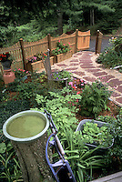 Shade garden backyard landscaping, flagstone patio walk path, wooden fence, windowboxes runner container pots, galvanized bucket tiny water garden, bird bath, old rustic ornaments sled, chair planter, flowers, evergreens, ferns, Dicentra, unusual and charming planter made from an old rocking chair