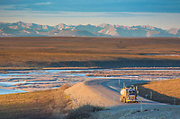 Semi tractor trailer travels the James Dalton Highway, adjacent to the Sag river and the distant Brooks mountain range, Arctic, Alaska.