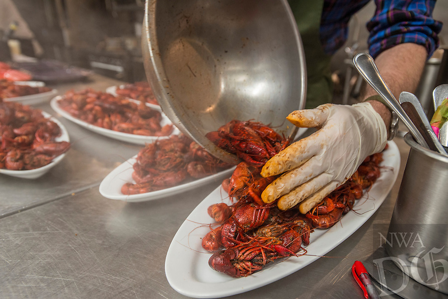 NWA Democrat-Gazette/ANTHONY REYES &bull; @NWATONYR<br /> Matthew McClure, executive chef at The Hive, plates boiled crawfish Wednesday, April 15, 2015 at a crawfish boil block party in Bentonville. Many boils happen this time of year. The Hive's boil featured a four course meal with crawfish flown in fresh from the gulf coast. Chef Matt McClure created each dish.