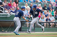 Sam Hilliard (25) of the Asheville Tourists slaps hands with third base coach Warren Schaeffer after hitting a home run against the Kannapolis Intimidators at Intimidators Stadium on May 28, 2016 in Kannapolis, North Carolina.  The Intimidators defeated the Tourists 5-4 in 10 innings.  (Brian Westerholt/Four Seam Images)