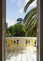 A pair of bright yellow garden chairs have been placed on the balcony