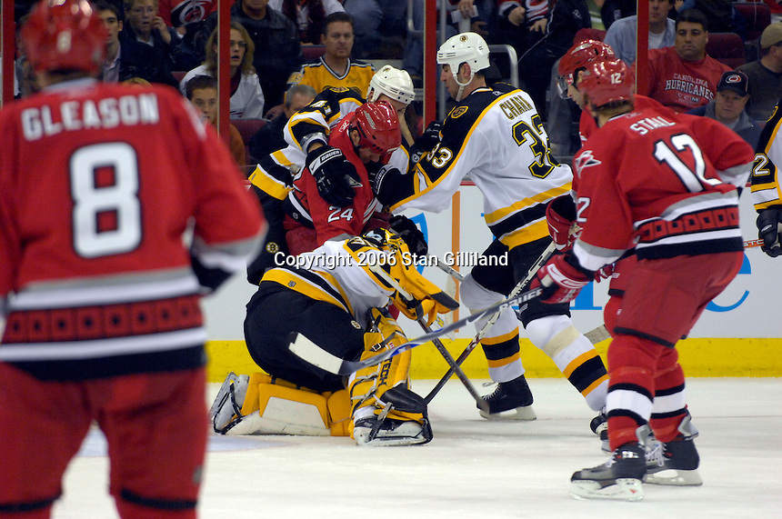 The Boston Bruins' goalie Tim Thomas, Andrew Alberts (41) and Zdeno Chara (33) defend as  the Carolina Hurricanes' Scott Walker, center, enters the crease during an NHL hockey game Saturday, Dec. 2, 2006 in Raleigh, N.C. Carolina won 5-2.<br />
