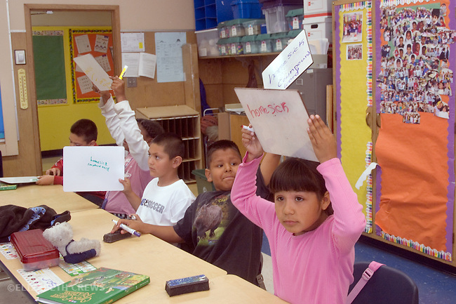 Oakland CA 2nd graders being tested on spelling knowledge by writing words on dry erase boards and showing them to teacher