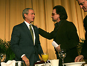 United States President George W. Bush, left, and rock singer, activist Bono, right, embrace after Bono speaks at the National Prayer Breakfast in Washington,DC on February 2, 2006.  The man on the right is United States Senator Mark Pryor (Democrat of Arkansas).  <br /> Credit: Dennis Brack - Pool via CNP