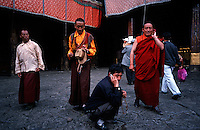 A Tibetan pilgrim chats on a mobile phone while visiting Jokhang, the most holy temple of Tibet in Lhasa..