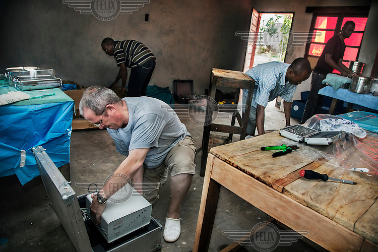 Dr Richard Hardi and his ophthalmology team pack their equipment as they prepare to leave the remote village of Pania where they have been running a cataract clinic. <br /> <br /> From his base in Mbuji Mayi Hungarian ophthalmologist Friar Richard Hardi and his team travelled deep into the Congolese rainforest, by 4x4 and canoe, to treat people in isolated communities most of whom have never seen an ophthalmologist. At a small village called Pania they established a temporary field hospital and over the next three days made hundreds of consultations. Although both conditions are preventable, many of the patients they saw had Glaucoma or River Blindness (onchocerciasis) that had permanently damaged their eyesight. However, patients with cataracts, a clouding of the eye's lens, who were suitable for treatment were booked for an operation. For two days the team carried out the ten minute procedure on one patient after another. The surgery involves making a 2.2mm incision into the remove the damaged lens that is then replaced by an artificial one. Doctor Hardi is one of the few people willing to make such a journey but is inspired to do so by his faith and, as he says: 'Here I feel that I can really make a difference in people's lives'. /Felix Features