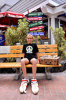11 year old child sitting outside Bubba Gump restaurant in Kailua-Kona. Big Island, Hawaii