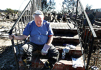 LOS ANGELES,CA - NOVEMBER 19,2008: Bob Atchison rests on the front porch as he searches what is left of his mother-in-laws home at Oakridge mobile home park in Sylmar, November 19, 2008.