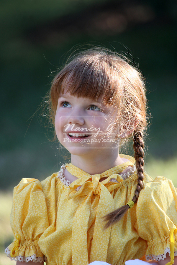 A happy young girl in a prairie dress