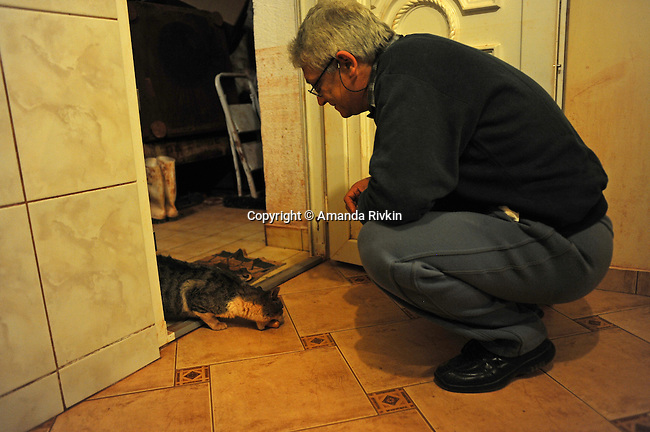Jozsef Szalai feeds a cat with sullied fur from his kitchen door after dinner in his home in the aftermath of a toxic industrial accident in a ruined section of Devecser, Hungary on November 20, 2010. On October 4, 2010, a rupture in a reservoir containing toxic alumina sludge in nearby Ajka, Hungary that sent hazardous red sludge gushing through Devecser and several surrounding towns, killing ten, injuring hundreds and leaving several families homeless; unlike other effected families, the Szalai family hopes to remain in their home as long as possible despite the devastation around them.