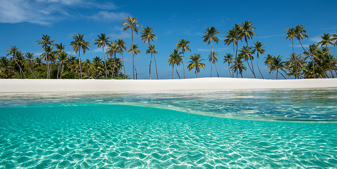 A unique view from above and below the aquamarine waters surrounding the white sand and palm trees on this picturesque island in the Indian Ocean.