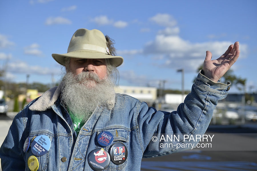 """Merrick, New York, USA. October 23, 2016. FRED S. CHANDLER, 66, of North Bellmore, wearing several political campaign buttons supporting Democratic presidential candidate Hillary Clinton, gestures with hand while talking during rally to demand public water and stop New York American Water (NYAW) rate hike. On denim jacket were buttons for Hofstra University DEBATE 2016 - and """"So My Daughter Knows She Can Be President. Hillary 16"""" - """"TRUMPBUSTERS"""" - """"CLINTON KAINE 16"""" - and Monopoly Man character with """"NEVER TRUMP"""" text."""