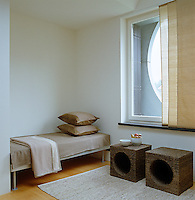 A sparse and unwelcoming guest bedroom with a vertical sliding blind across the circular window