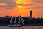 Sunset over downtown Charleston South Carolina with st Phillips church steeple schooner pride sailboat