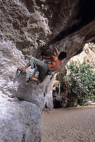 Local Thai climber bouldering on severely overhanging wall at Phra Nang Beach, Railay Rei Lei, Thailand