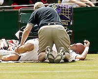 29-6-06,England, London, Wimbledon, second round match,  Melle van Gemerden tijdens een fysio behandeling i.v.m. rugpijn in zijn partij tegen Fish