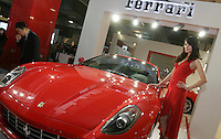 A model stands beside a Ferrari at The Beijing International Automobile Exhibition..19 Nov 2006