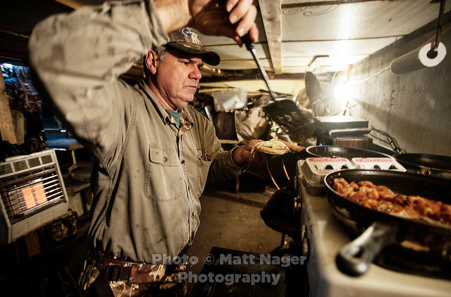 Lynn Berggren (cq) cooks breakfast in his duck blind during a hunting trip just off the duck-rich Platte River in Nebraska, Saturday, December 3, 2011...Photo by Matt Nager
