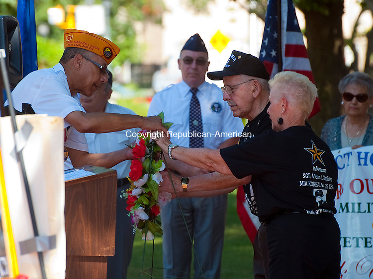 WATERBURY, CT--- -072515JS03--Donald and Claire George of Waterbury, hand a wreath for Korean War Veterans to Sam Beamon, Chairman of the Waterbury Veterans Memorial Committee during the 18th Annual Korean War Veterans Remembrance Day ceremony Saturday on the Waterbury Green. <br /> Jim Shannon Republican-American