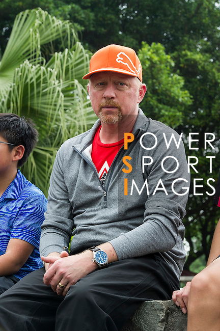 Tennis Legend Boris Becker (orange cap) observes and gives tips to junior tennis players at Mission Hills Resort on 19 March 2016, in Shenzhen, China. Photo by Lucas Schifres / Power Sport Images