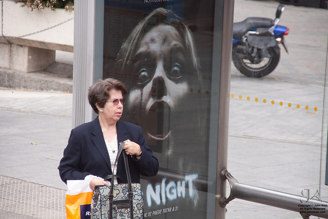 Humor in Horror of a movie poster lurking behind an unsuspecting woman