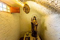 "Inside the cave church ""Cueva Santa de la Virgen de Gracia"" in the Barrio de Cuevas section of Guadix, Granada Province, Andalusia, Spain."