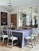 In the family room, the 18th-century chairs around the dining table are Swedish, the 19th-century gilt bronze-and-crystal chandeliers are French. The ceilings throughout are painted in Farrow & Ball's All White. The mirrored wall gives a sense of space.