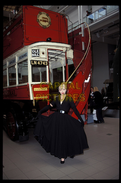 TAMARA BECKWITH.Ref:4564.black dress, 50's style, long black gloves, black belt, bus, tram, full length, full-length.RAW SCAN - PHOTO WILL BE ADJUSTED FOR PUBLICATION.www.capitalpictures.com.sales@capitalpictures.com.©Capital Pictures.