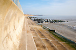Curved wave return sea wall, steps and rock armour groynes, forming coastal defences at Southwold, Suffolk, England