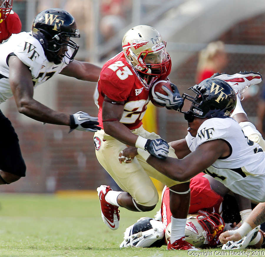 TALLAHASSEE, FL 9/25/10-FSU-WF FB10 CH-Wake Forest's Gelo Orange, left, and Kris Redding bring down Florida State's Chris Thompson during first half action Saturday at Doak Campbell Stadium in Tallahassee. .COLIN HACKLEY PHOTO